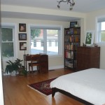 Large windows in bright sunny master bedroom